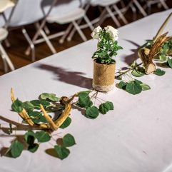 burlap cans with antlers and flowers and leaves for wedding table decorations antler and wood round cake stands and servers for rent for rustic montana wedding